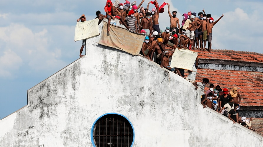 Inmates protest on the top of a prison building, in Colombo