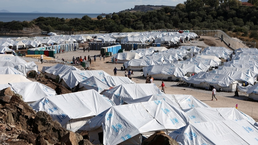 Refugees and migrants make their way in the Kara Tepe camp on the island of Lesbos