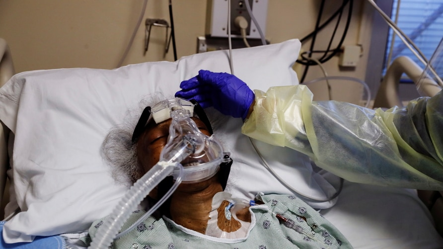 Florence Bolton, 85, a coronavirus disease (COVID-19) positive patient, has her head touched by registered nurse Alma Abad as she lies in her intensive care bed at Roseland Community Hospital on the South Side of Chicago, Illinois