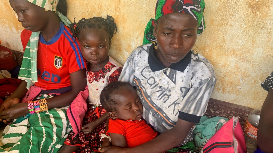 FILE PHOTO: A woman who fled the violent rebellion in Central African Republic (CAR) sits with her family as they wait for their identification process in the border town of Garoua Boulai