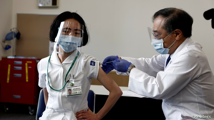 A medical worker receives a dose of the coronavirus disease (COVID-19) vaccine as the country launches its inoculation campaign, in Tokyo