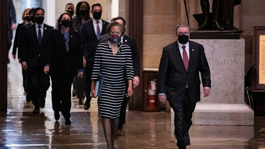FILE PHOTO: House impeachment managers walk the article of impeachment against former U.S. President Donald Trump through the Rotunda of the U.S. Capitol