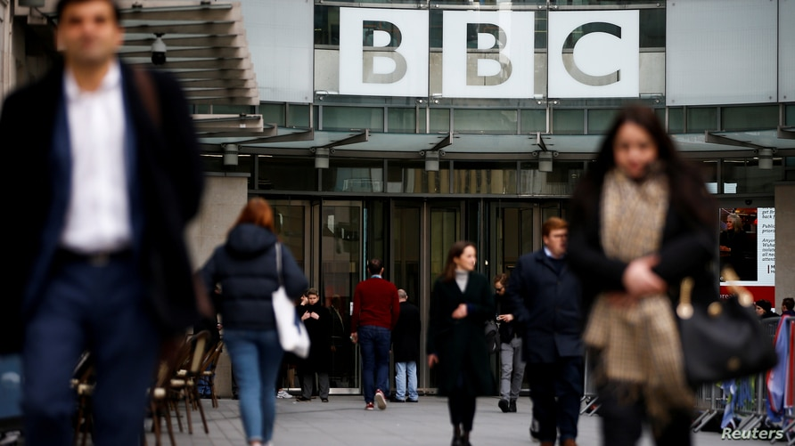 FILE PHOTO: Pedestrians walk past a BBC logo at Broadcasting House, as the corporation announced it will cut around 450 jobs from its news division, in London