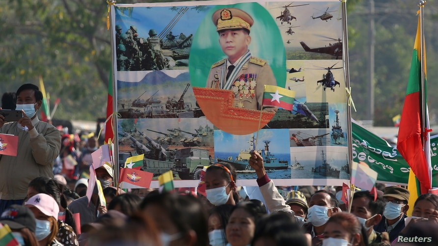 Military supporters carry a portrait of junta leader General Min Aung Hlaing as they celebrate the coup in Naypyitaw