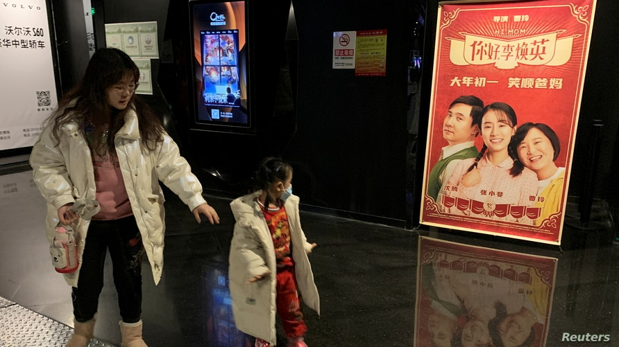 "People walk past a poster for Chinese movie ""Hi Mom"" at a cinema in Beijing"