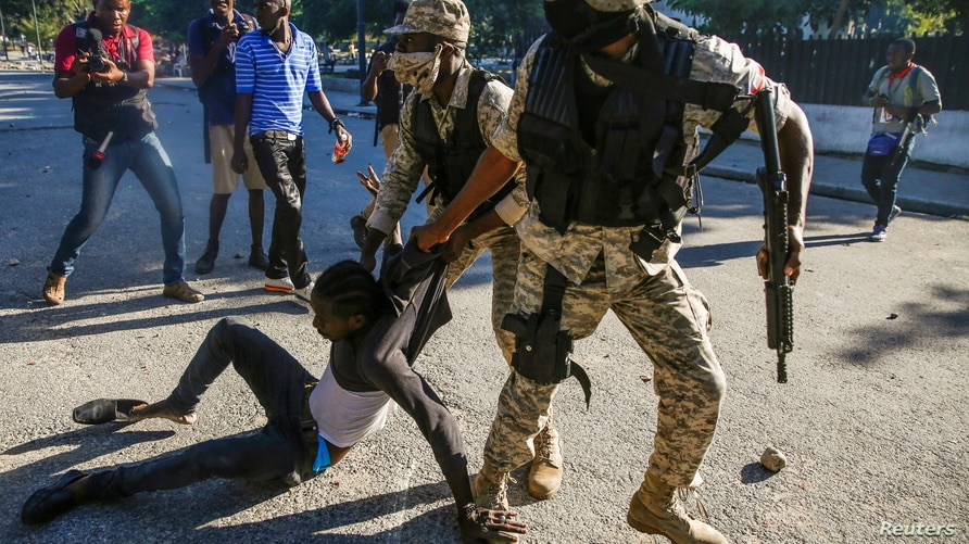 Police officers detain a man during protests against Haiti's President Jovenel Moise, in Port-au-Prince