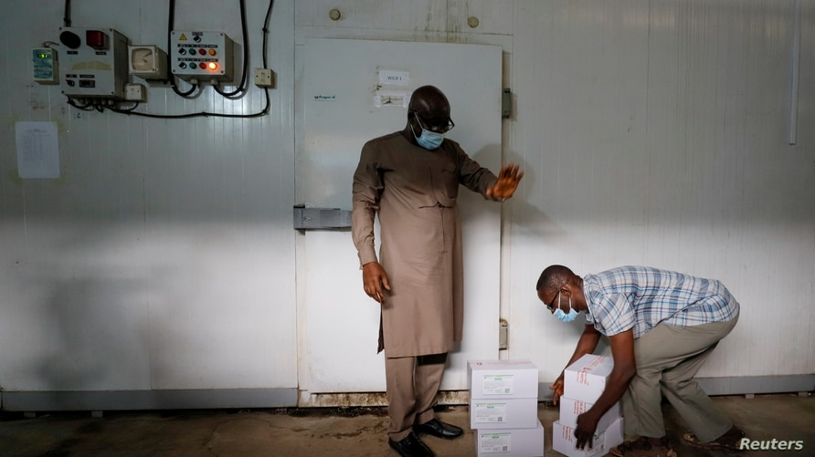 A worker prepares to store boxes of vaccines in a cold room as the country receives its first batch of coronavirus disease (COVID-19) vaccines under COVAX scheme, in Accra