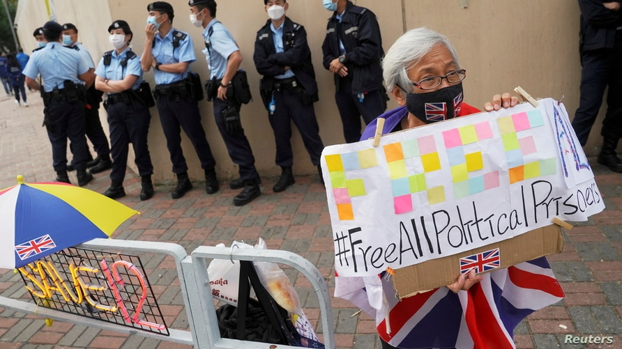 Pro-democracy supporter holds a sign calling for the release of all political prisoners outside Tin Shui Wai police station in Hong Kong
