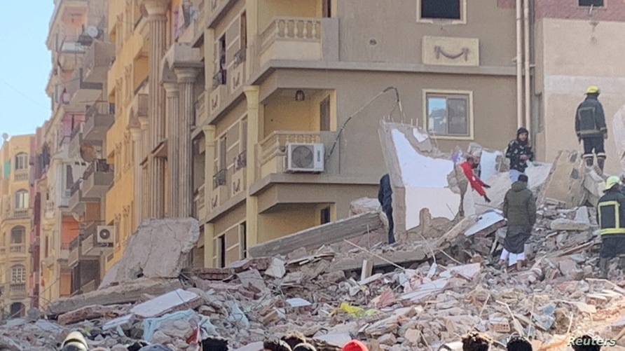 People inspect the area where a building was collapsed in Gesr al-Suez, Cairo