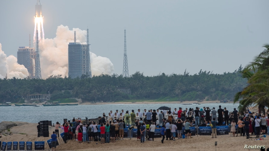 People watch from a beach as the Long March-5B Y2 rocket, carrying the core module of China's space station Tianhe, takes off from Wenchang
