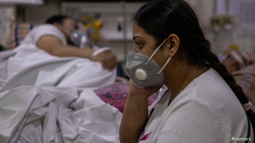 Manika Goel, sits next to her husband who is suffering from the coronavirus disease (COVID-19) inside the emergency ward at Holy Family hospital in New Delhi