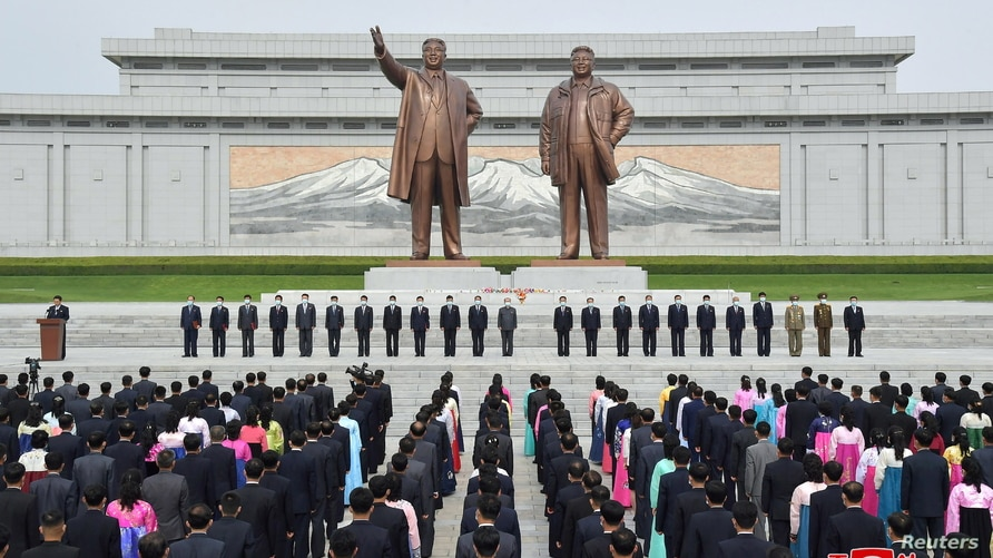 Attendees wearing face masks participate in an oath-taking meeting on Mansu Hill in Pyongyang