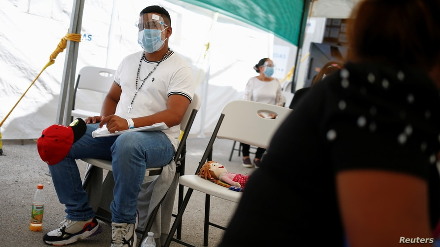 Asylum seekers, under the Migrant Protection Protocols (MPP) program, wait at the Leona Vicario temporary migrant shelter, before being transferred to continue their asylum request in the United States, in Ciudad Juarez