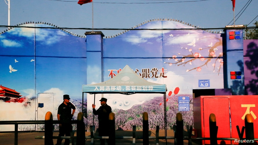 FILE PHOTO: Security guards stand at the gates of what is officially known as a vocational skills education centre in Huocheng County