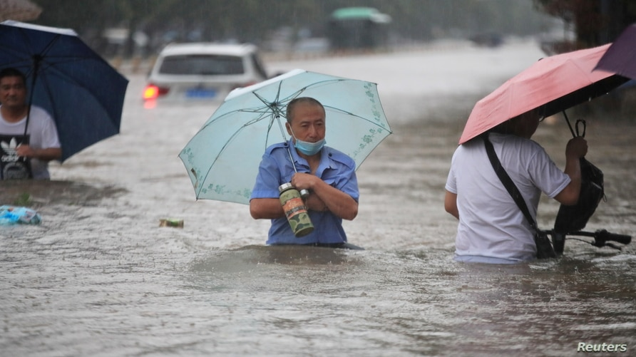 Residents wade through floodwaters on a flooded road amid heavy rainfall in Zhengzhou