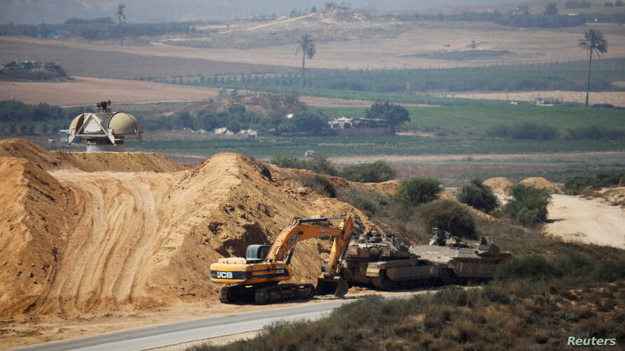 An Israeli military armoured personnel carrier (APC), a tank and a bulldozer are seen next to the border with the Gaza Strip, in southern Israel July 11, 2019. REUTERS/Amir Cohen
