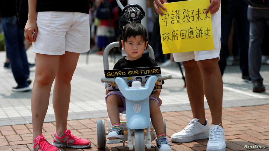 """A family participates in a protest rally titled """"Guard Our Children's Future"""" at Edinburgh Place in Hong Kong, Aug. 10, 2019."""