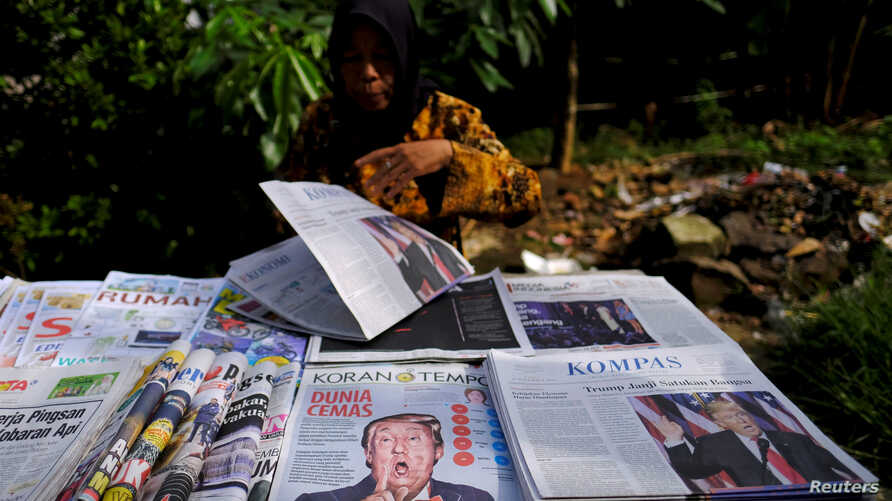 A newspaper seller prepares her stall with articles dominated by the election of U.S. Republican Donald Trump, in Jakarta, Indonesia November 10, 2016. REUTERS/Beawiharta