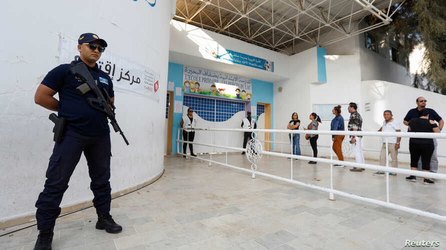 A police officer stands guard as people queue to cast their vote outside a polling station during a second round runoff of a…