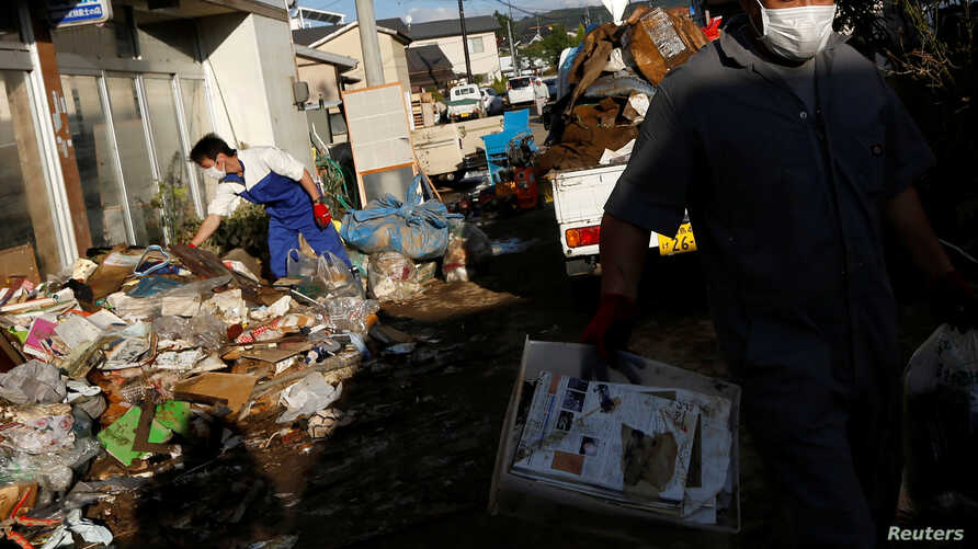 Locals clean a house, in the aftermath of Typhoon Hagibis, in Yanagawamachi district, Date City, Fukushima prefecture, Japan…