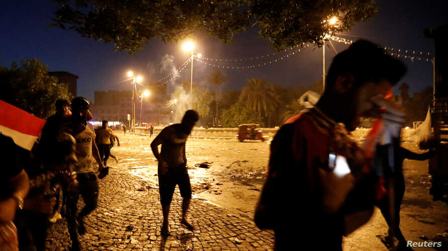 Demonstrators run away from tear gas fired by Iraqi security forces during a protest over corruption, lack of jobs, and poor…