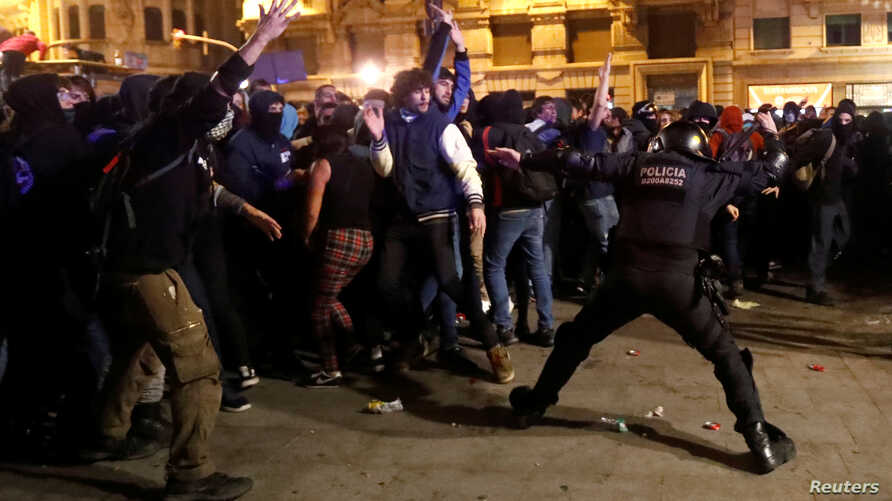 Catalan pro-independence demonstrators and riot police clash during a protest against police action, in Barcelona, Spain,…