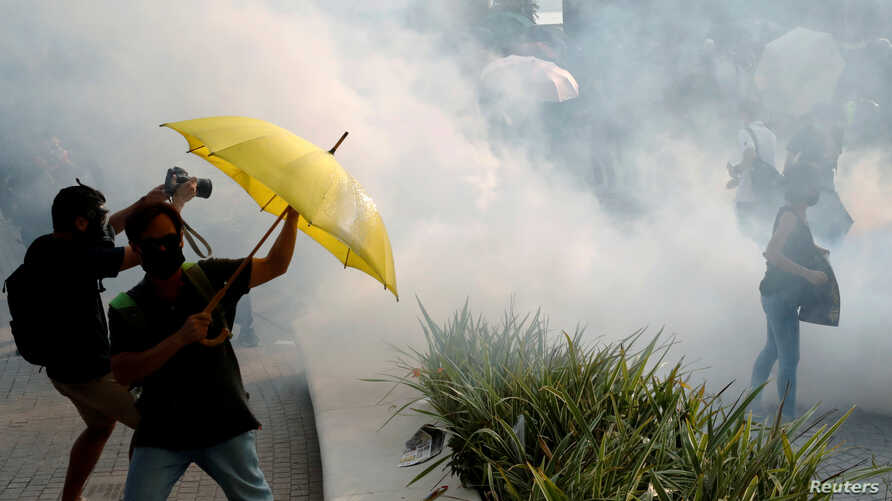 Anti-government demonstrators are seen among the tear gas during a protest in Hong Kong's tourism district of Tsim Sha Tsui,…