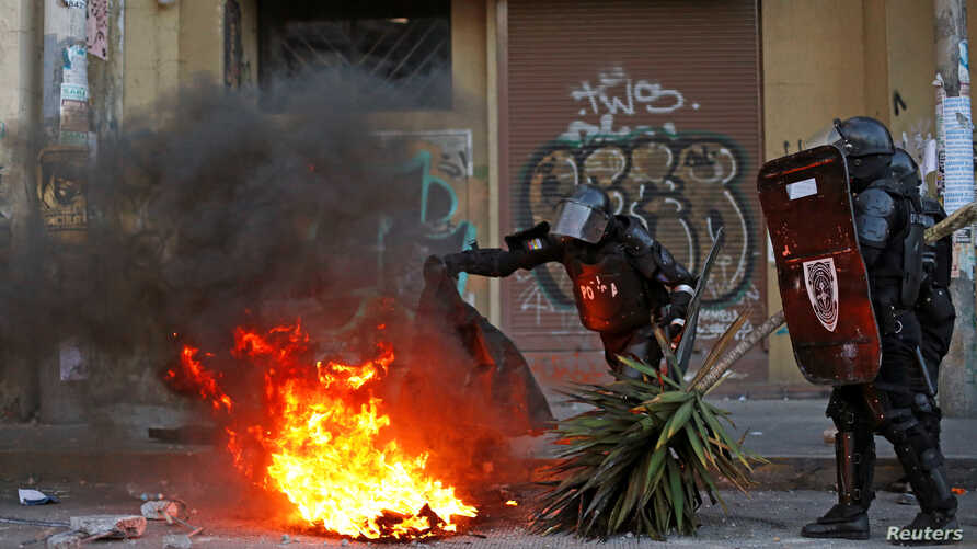 Riot police patrol remove a burning barricade set by demonstrators during protests after Ecuador's President Lenin Moreno's…