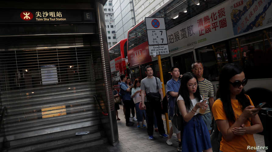 People queue as they wait for the bus, next to a suspended metro station in Tsim Sha Tsui district, in Hong Kong, China October…