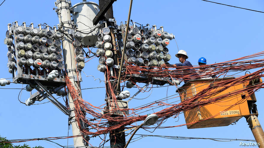 Filipino lineworkers repair power meters atop electricity post at the main street of Quiapo city, metro Manila, Philippines…