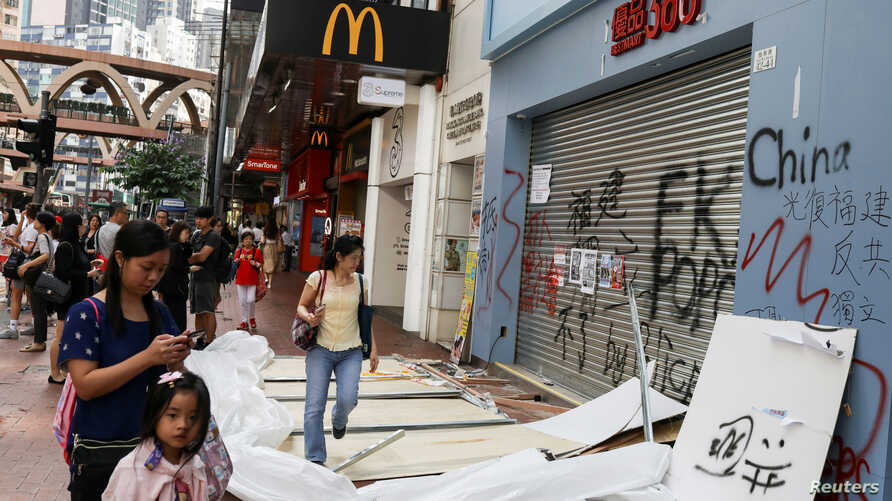 FILE PHOTO: People walk past a vandalised store in Causeway Bay district, in Hong Kong, China October 8, 2019. REUTERS/Susana…