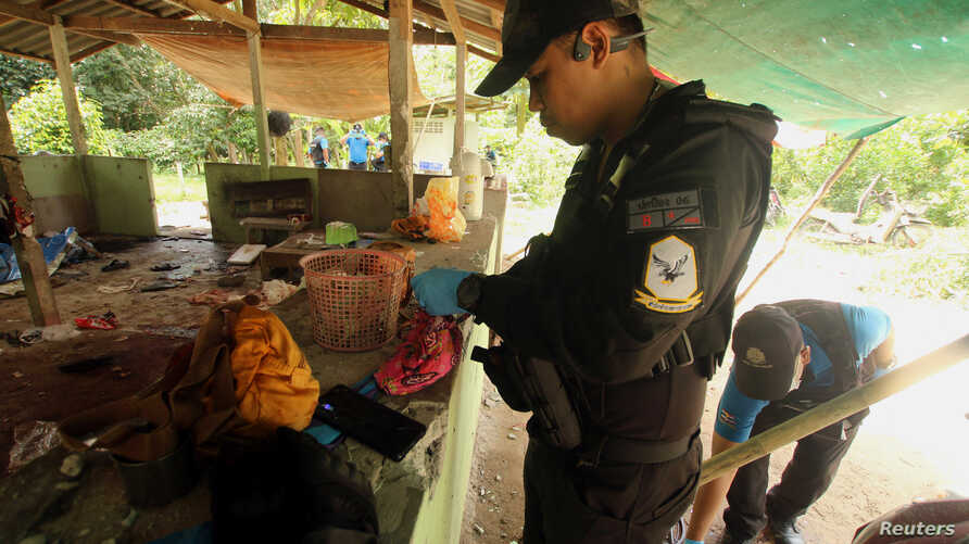 A Thai forensic expert and a military personnel examine the site where village defence volunteers were killed by suspected…