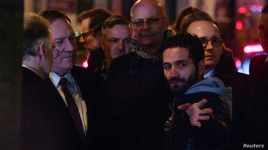 U.S. Secretary of State Mike Pompeo speaks with Izzet Cagan, owner of the Doner kebab shop where one person died in Halle,…