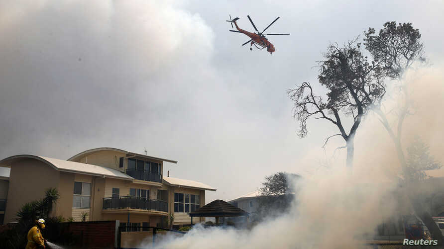 A fire bombing helicopter works to contain a bushfire along Old Bar road in Old Bar, New South Wales, Australia November 9,…