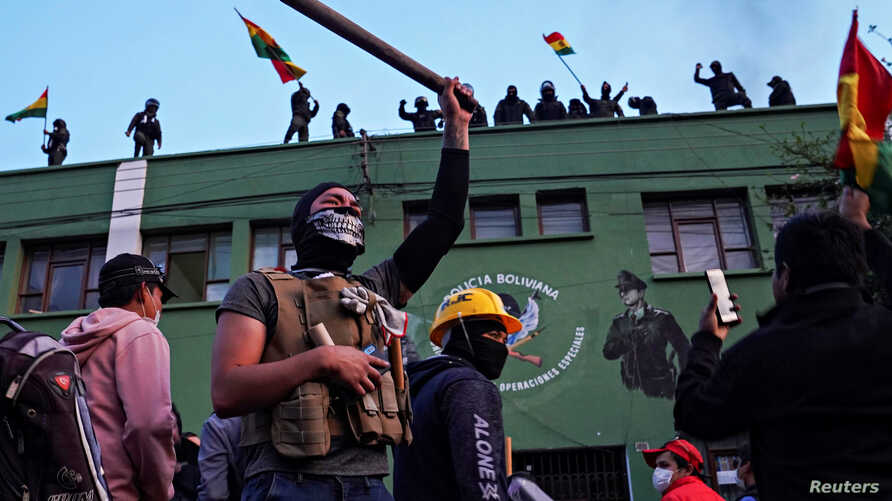 Opponents to Bolivia's President Evo Morales react as police officers stand on the roof of their headquarters, in Cochabamba,…