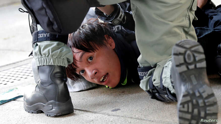 A protester is detained by riot police officers during an anti-government demonstration in Hong Kong, China, November 10, 2019…