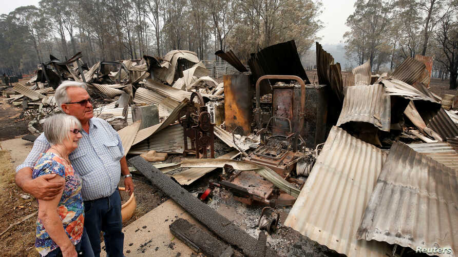 Lyn and Peter Iverson with their burnt out office and shed on their property at Half Chain road, Koorainghat, Australia,…