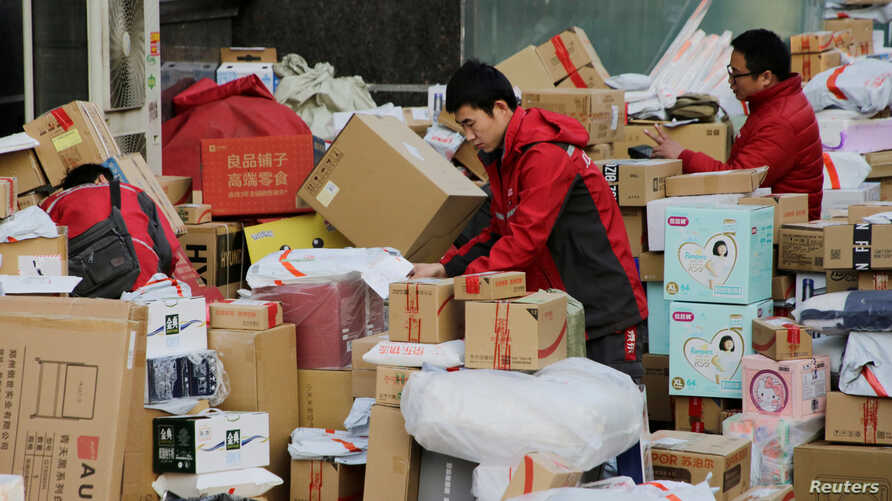 Deliverymen of JD.com work among parcels beside a road after the 11.11 Singles' Day shopping festival in downtown Beijing,…