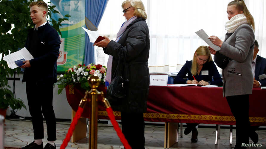 People queue to cast their vote at a polling station during the parliamentary election in Minsk, Belarus November 17, 2019…