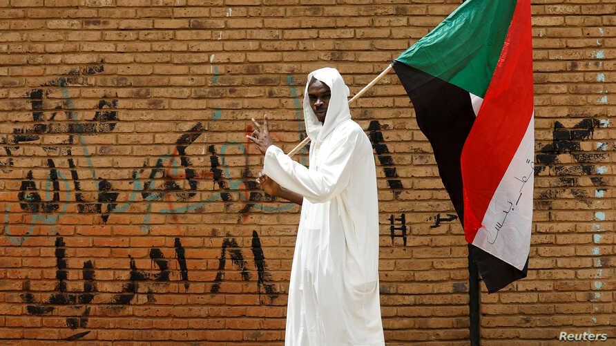 FILE PHOTO: A protester makes victory sign as he carries a Sudanese flag in front of the Defence Ministry in Khartoum, Sudan,…