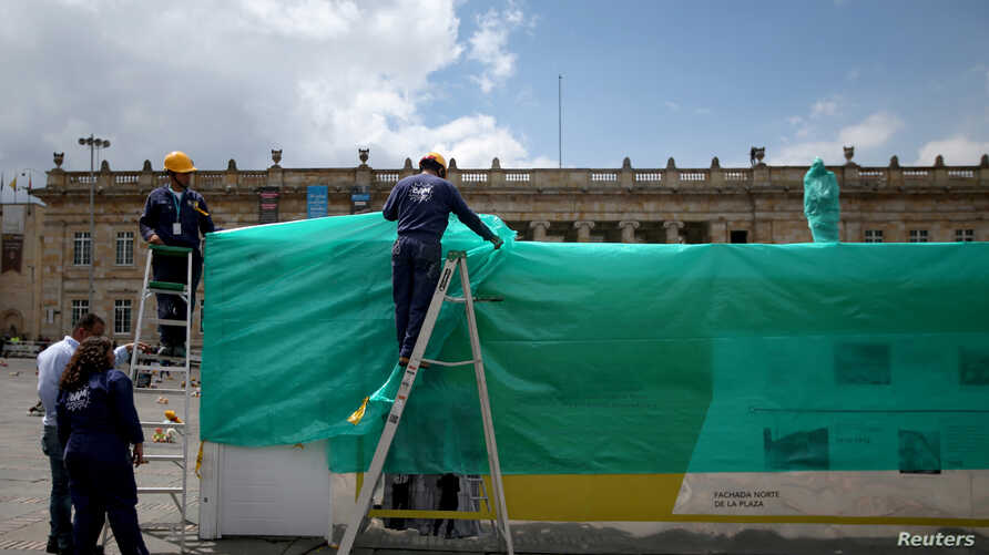 Workers cover the statue of Simon Bolivar in Bogota with plastic, one day before a national strike in Bogota, Colombia November…