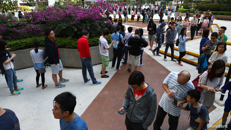 Voters queue to vote at a polling station during district council local elections on Hong Kong Island, China November 24, 2019…