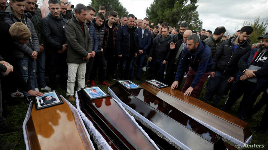 Relatives surround some of the coffins during the funeral of six members of the Cara family, killed during an earthquake that…