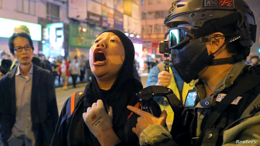 A protester is detained by a riot police officer during an anti-government rally outside Prince Edward MTR station in Hong Kong…