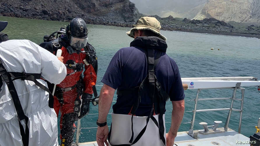 Members of a dive squad conduct a search during a recovery operation around White Island, which is also known by its Maori name…
