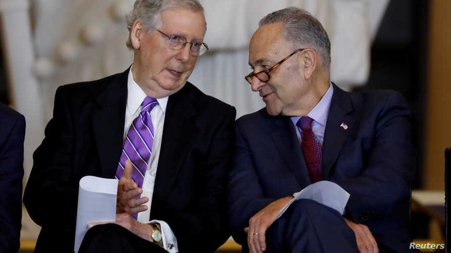 FILE PHOTO: Senate Majority Leader Mitch McConnell and Senate Minority Leader Chuck Schumer talk during a ceremony to present…