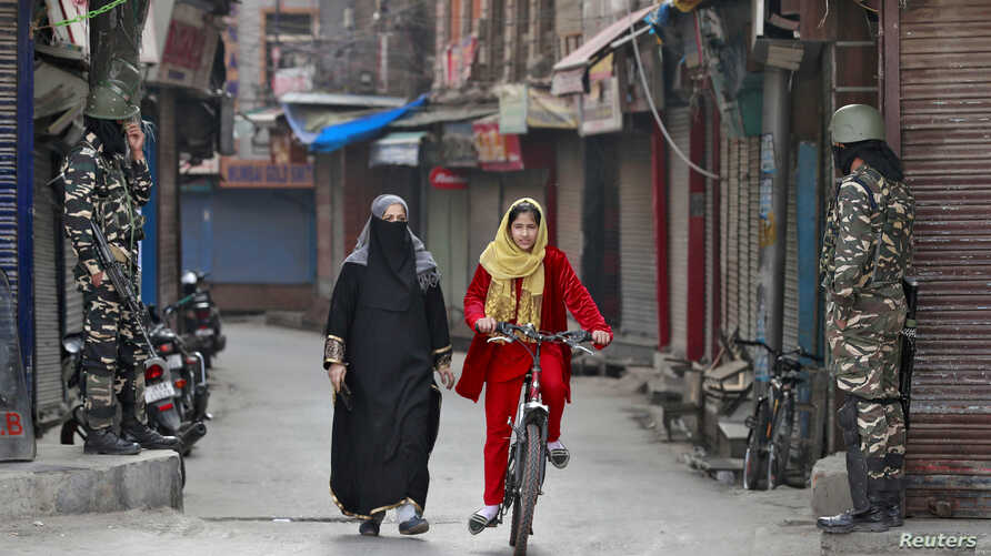FILE PHOTO: A Kashmir girl rides her bike past Indian security force personnel standing guard in front closed shops in a street…