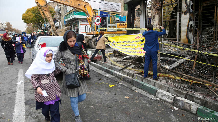 FILE PHOTO: People walk near a burnt bank, after protests against increased fuel prices, in Tehran, Iran November 20, 2019…