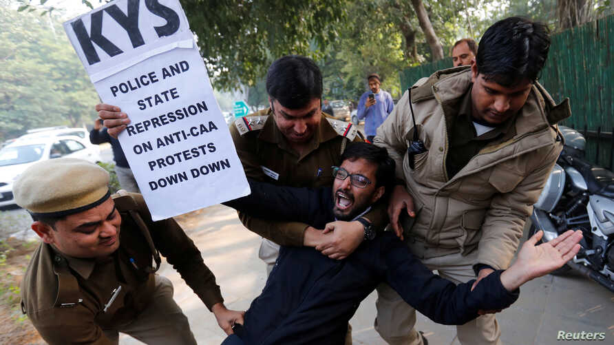 A demonstrator is detained by police outside the Assam bhawan (building) during a protest against a new citizenship law, in New…
