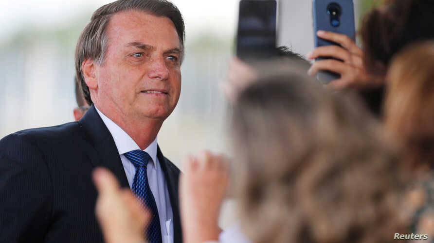 FILE PHOTO: Brazil's President Jair Bolsonaro poses for pictures as he leaves the Alvorada Palace in Brasilia, Brazil December…